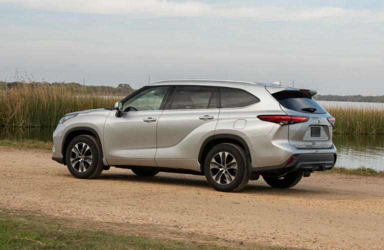 A left profile photo of the 2020 Toyota Highlander parked by a marsh.