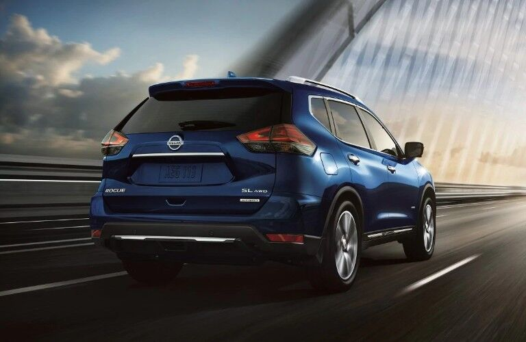 Rear passenger angle of a blue 2019 Nissan Rogue driving on a bridge towards a sunset