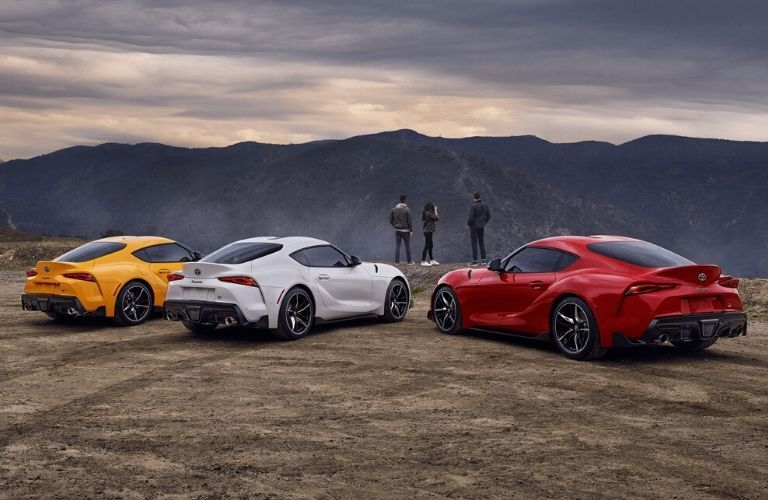 Exterior view of the rear of three 2020 Toyota Supra models parked on a cliff side