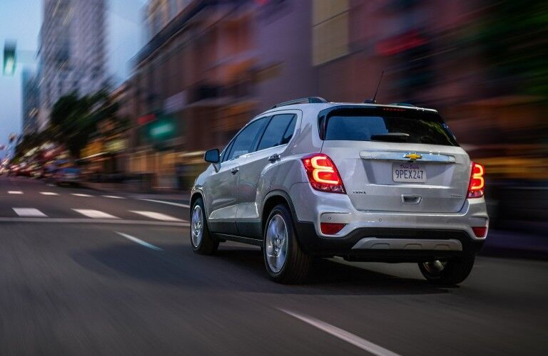 Rear driver angle of a silver 2020 Chevrolet Trax driving down a city street