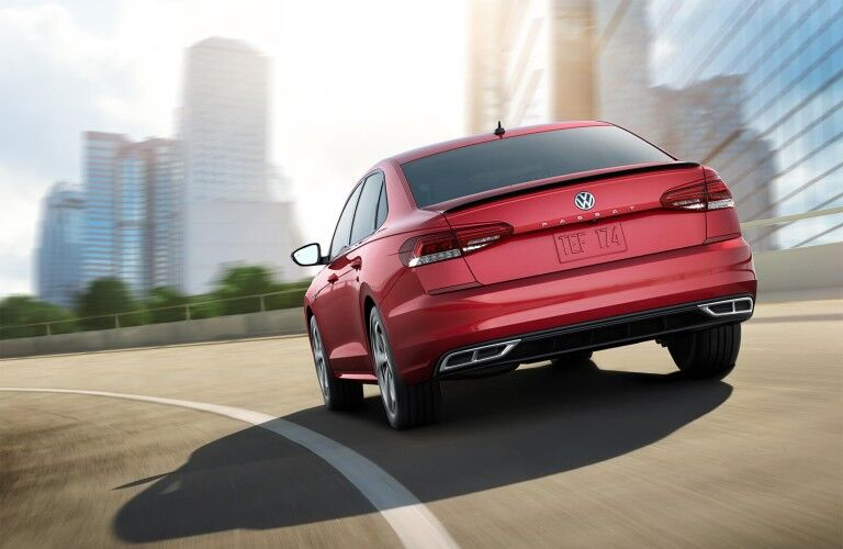 Rear driver angle of a red 2020 Volkswagen Passat driving towards a city