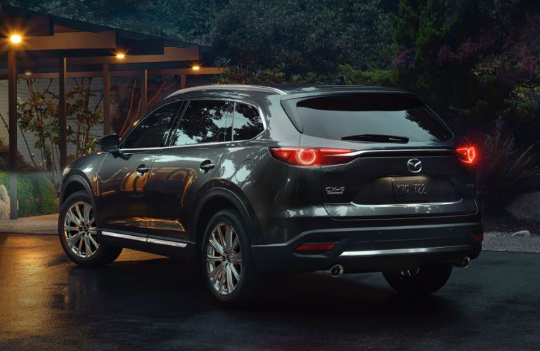 The rear and side view of a dark gray 2021 Mazda CX-9.