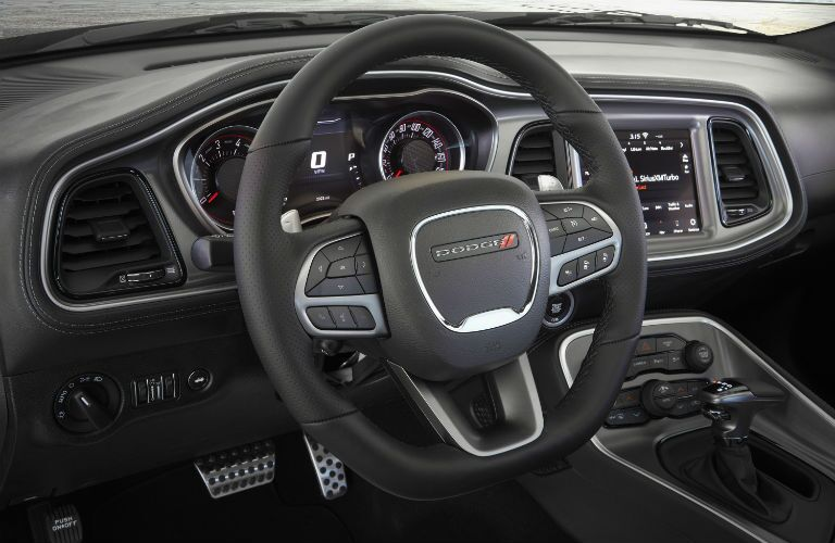 The steering wheel and intrument cluster inside a 2020 Dodge Challenger.
