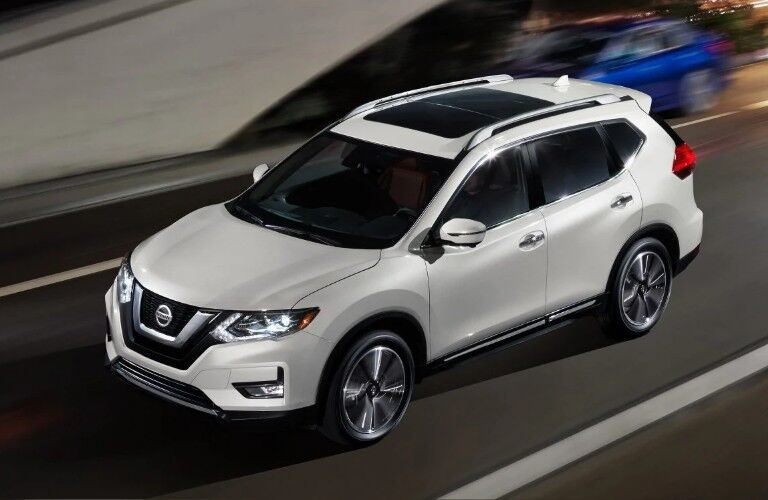 Front driver aerial angle of a white 2019 Nissan Rogue driving on a road