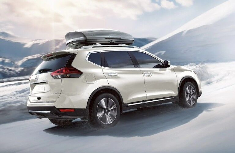 Rear passenger angle of a white 2019 Nissan Rogue driving through snow