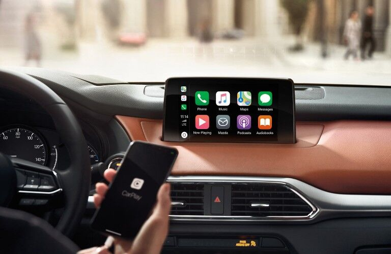 Close up of the MAZDA CONNECT™ infotainment system with Apple CarPlay® being used inside the 2019 Mazda CX-9