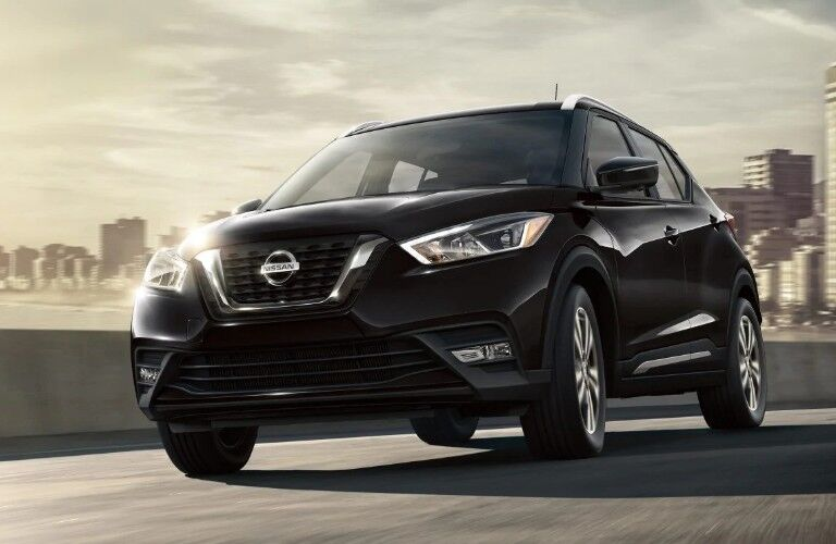 Front driver angle of a black 2019 Nissan Kicks driving down a road with a city skyline in the background