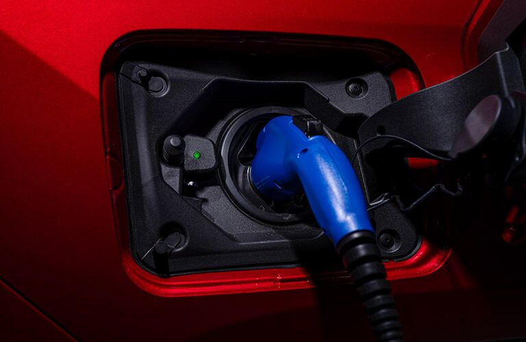 A charger inserted into a red 2021 Toyota RAV4 Prime