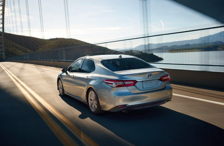 Rear driver angle of a silver 2020 Toyota Camry driving on a bridge