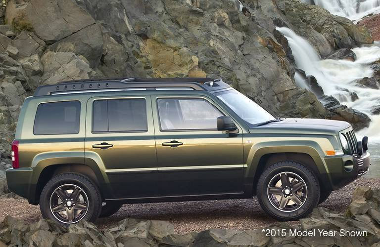 The side view of a green 2016 Jeep patriot driving off-road.