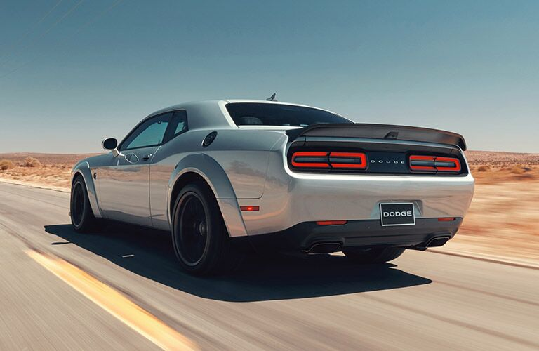 Rear driver angle of a white 2019 Dodge Challenger SRT Hellcat driving down a desert road