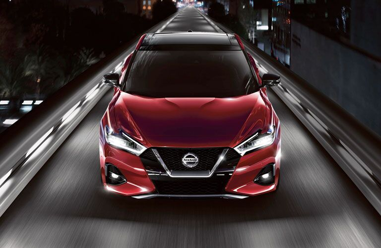 Red 2020 Nissan Maxima driving down a lit ramp in a dark room