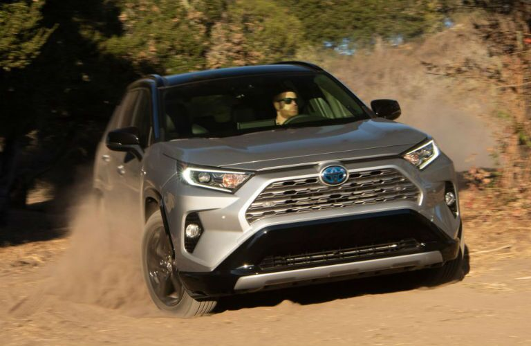 A head-on photo of the 2021 Toyota RAV4 Hybrid driving through sand.