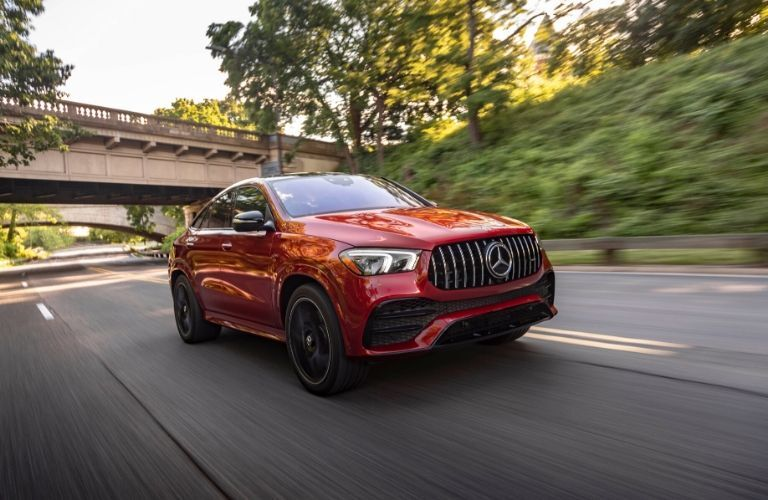 2021 MB GLE Coupe exterior front fascia passenger side on highway with trees and a bridge in the background