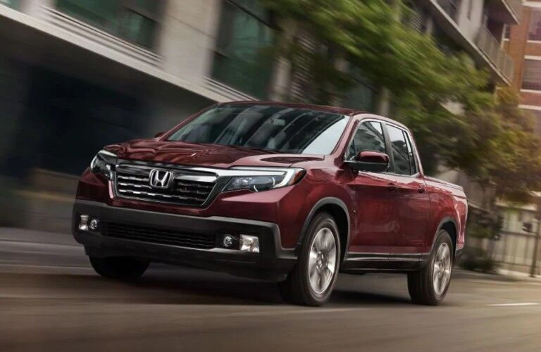 Front driver angle of a red 2019 Honda Ridgeline driving through a city
