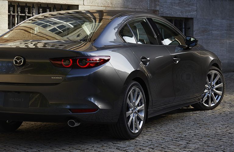 The rear and side view of a gray 2021 Mazda3 Sedan.