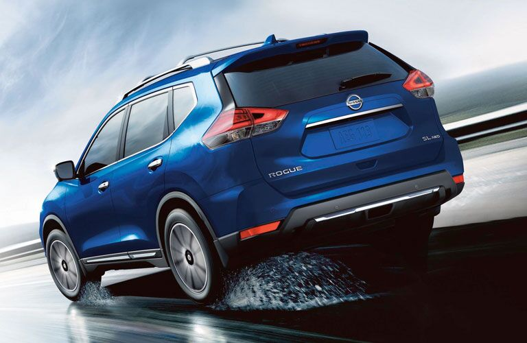 Rear view of blue 2020 Nissan Rogue driving on a wet road
