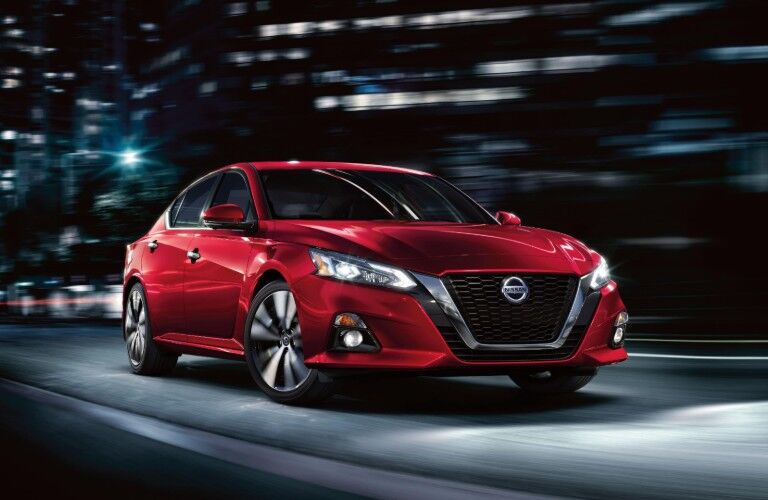 Front passenger angle of a red 2020 Nissan Altima driving through a city at night