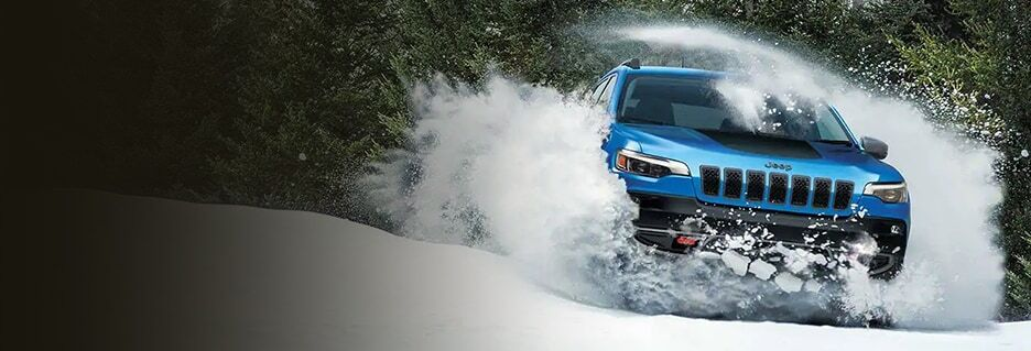 Blue Jeep Cherokee driving in snow