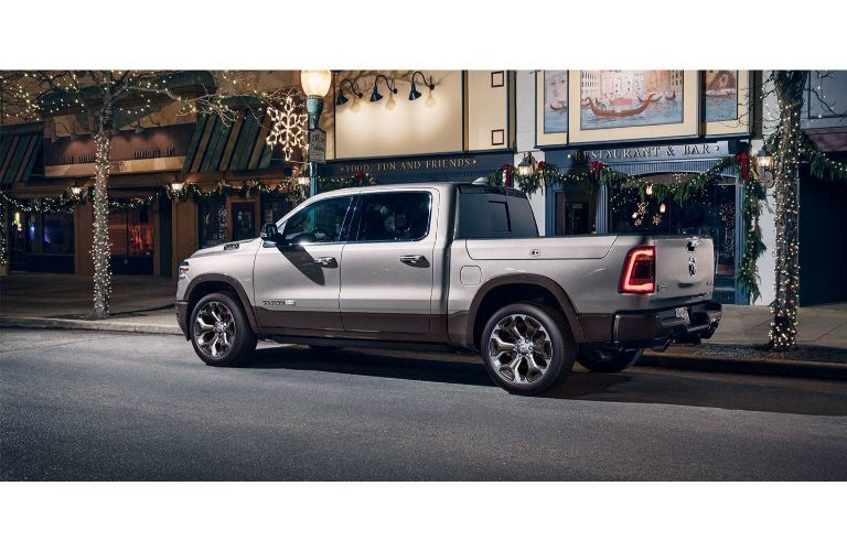 2020 Ram 1500 exterior side shot with gray silver paint color parked on a city street at night surrounded by winter and Christmas decorations