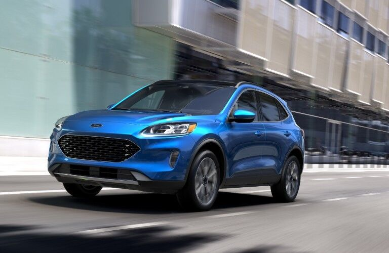 Front driver angle of a blue 2020 Ford Escape driving in the city