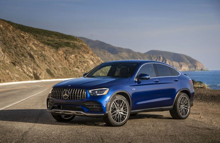 2020 MB AMG GLC Coupe exterior front cabin driver side on side of road with ocean and hill