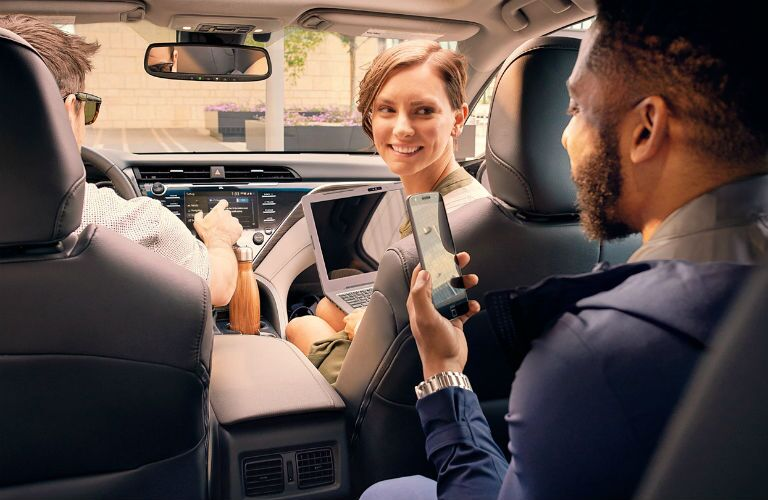 A photo of people using technology in the 2020 Toyota Camry.
