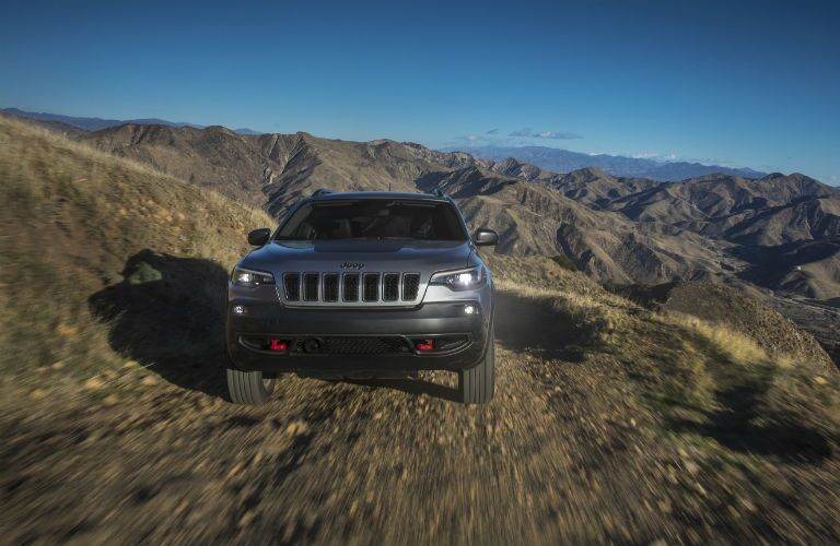 The front view of a gray 2021 Jeep Cherokee driving in rough terrain.