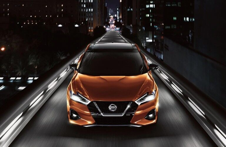 Front aerial angle of an orange 2020 Nissan Maxima driving through a city at night