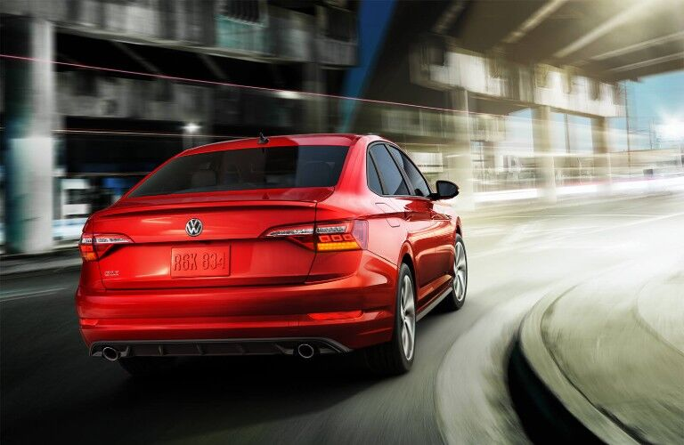 Rear passenger angle of a red 2019 Volkswagen Jetta GLI driving on a road