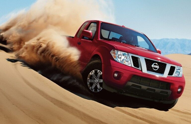 Front passenger angle of a red 2019 Nissan Frontier driving through heavy sand