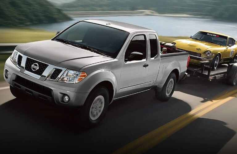 Front driver angle of a silver 2019 Nissan Frontier towing a trailer with a yellow car loaded on the trailer