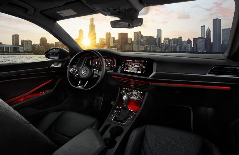 Red ambient lighting in the 2019 Volkswagen Jetta GLI with a city skyline in the background through the windshield
