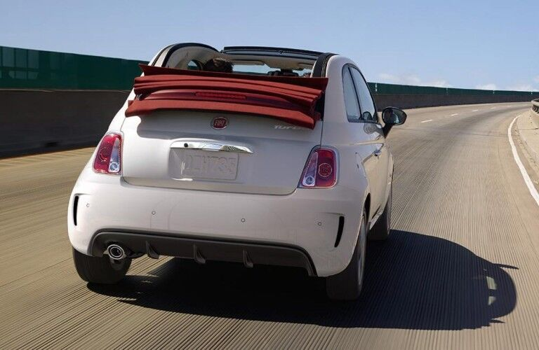 Rear passenger angle of a white 2019 FIAT 500 with its soft top down driving on a curving highway