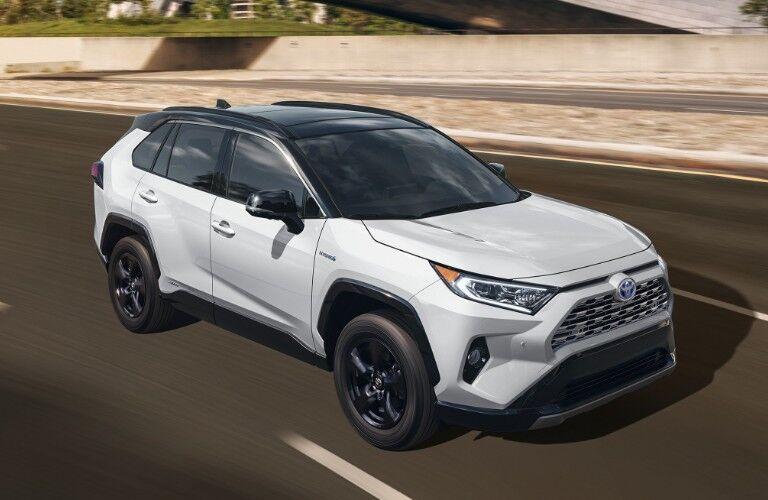 The front and side view of a white 2020 Toyota RAV4 driving down a road.