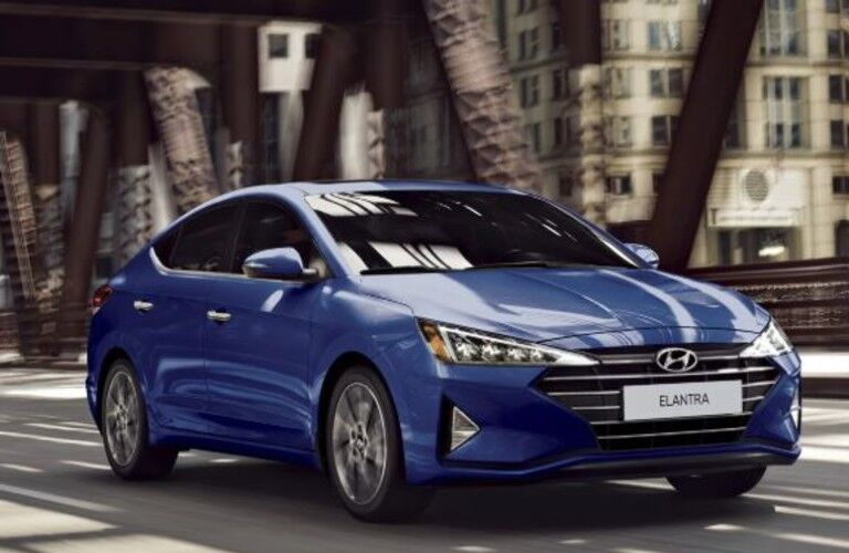 The front and side view of a blue 2020 Hyundai Elantra driving in a city.