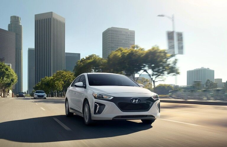 Front passenger angle of a white 2019 Hyundai Ioniq Electric driving in a city