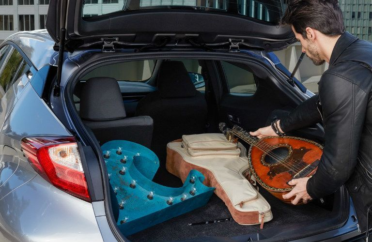 Man putting a guitar in the trunk of the 2018 Toyota C-HR