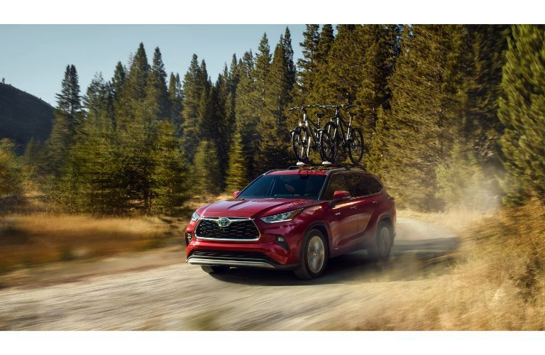 red 2021 Toyota Highlander driving through forest