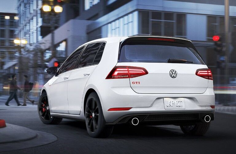 Rear driver angle of a white 2019 Volkswagen Golf GTI driving on a curvy city street