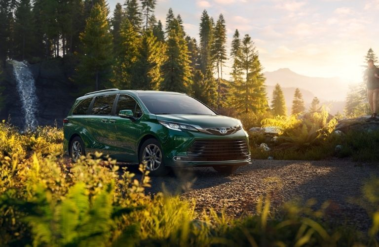 2021 Toyota Sienna in front of waterfall in the wilderness