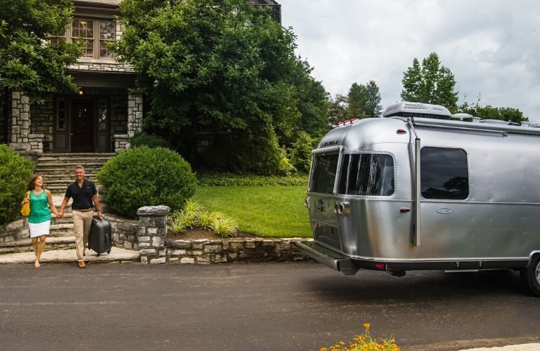 Image of a couple holding hands and walking near the rear of a silver 2020 Airstream Classic