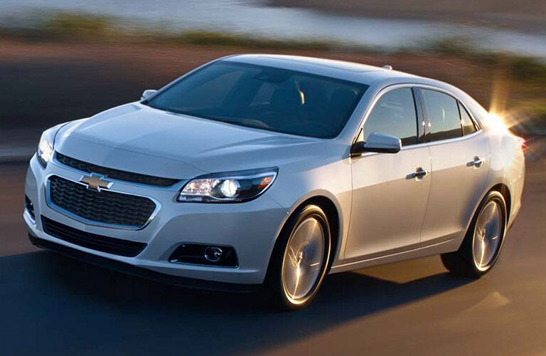 Front driver angle of a white 2014 Chevrolet Malibu driving on a road