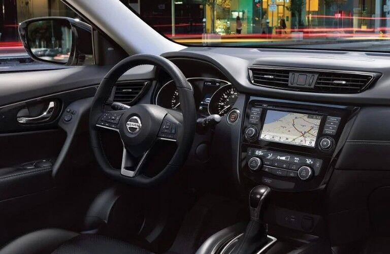 Front passenger angle of the black steering wheel, touchscreen, and dashboard in the 2019 Nissan Rogue