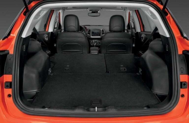 Rear view of the interior of an orange 2019 Jeep Compass with the rear seats folded down