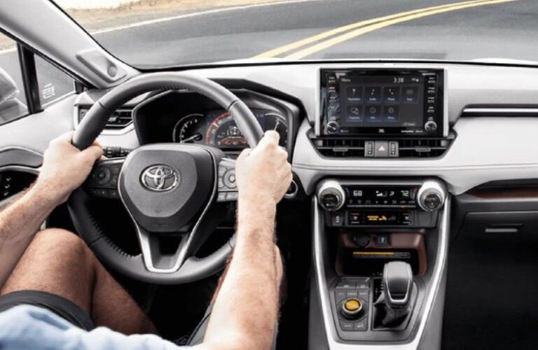 A man driving a 2021 Toyota RAV4 on a curved road with the steering wheel and touchscreen in view