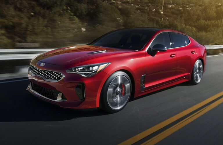 A red 2021 Kia Stinger driving down a road with wooded area in the background