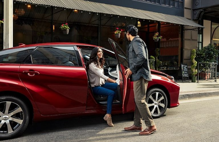 woman getting out of passenger side of 2020 Toyota Mirai and greeting a man