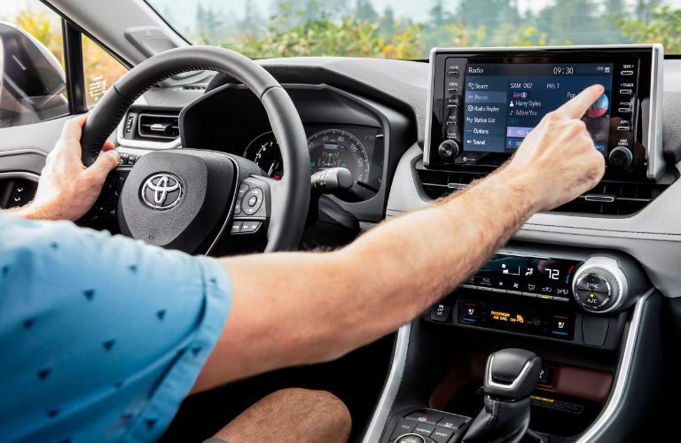 A photo of a person using the infotainment system in the 2021 Toyota RAV4.