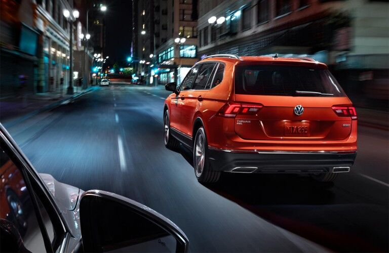 Rear driver angle of an orange 2019 Volkswagen Tiguan driving on a city street at night